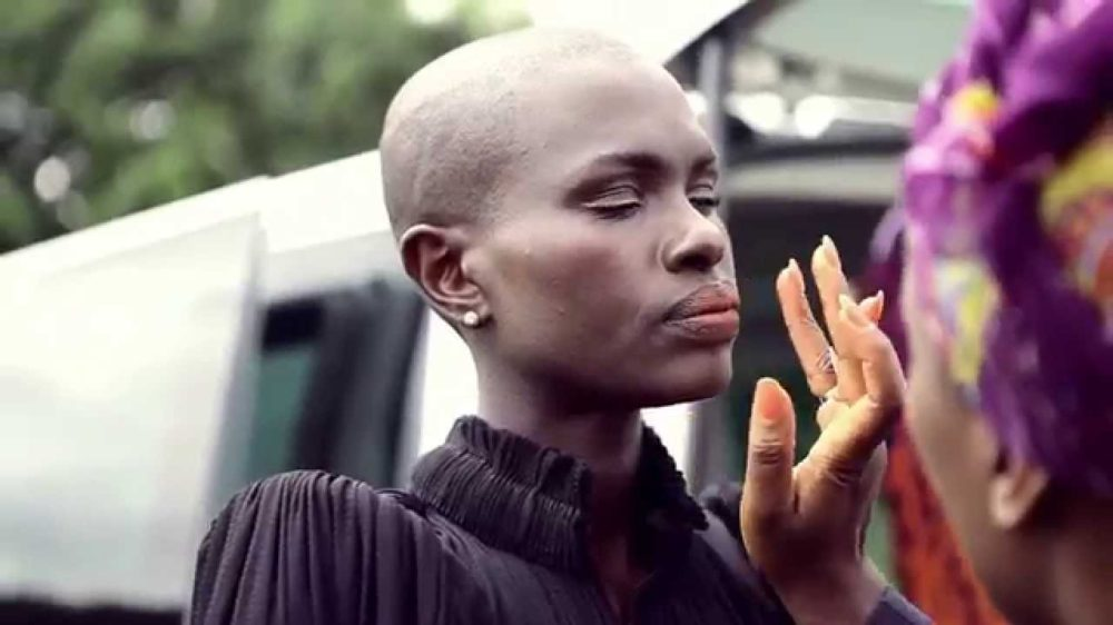 Ajuma Nasenyana assistant applying makeup outdoors on set