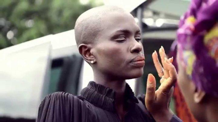 Ajuma Nasenyana African black Model assistant applying makeup outdoors on set
