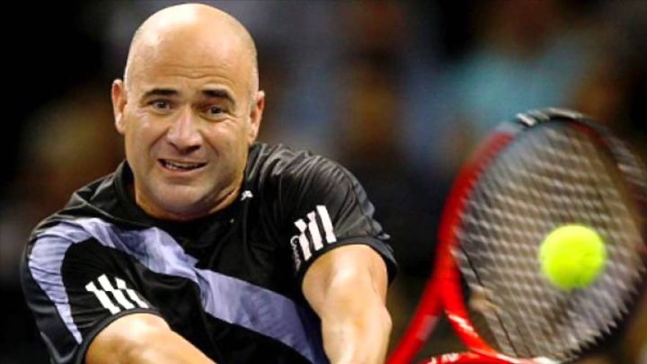 Andre Agassi tennis player that wore a wig hitting a tennis ball
