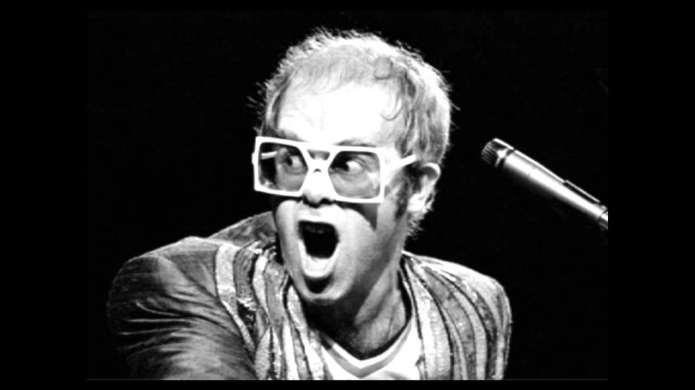 Elton John playing piano with receding hair and big specs