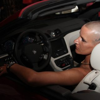 Eve Salvail model and actor with shaved head sitting in drivers seat of convertible top car
