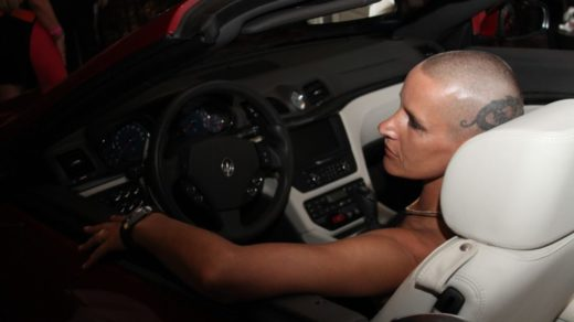 Eve Salvail sitting in drivers seat of convertible car with shaved head