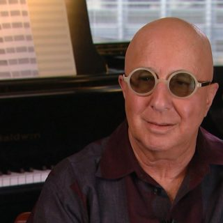Paul Shaffer musician with male pattern baldness being interviewed at home beside his piano