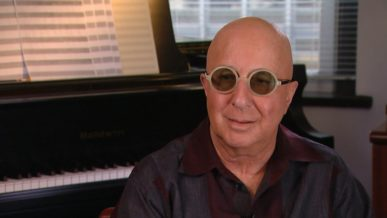 Paul Shaffer being interviewed at home wearing round glasses beside his piano