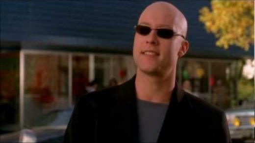 Michael Rosenbaum wearing dark sunglasses sporting a shaved head