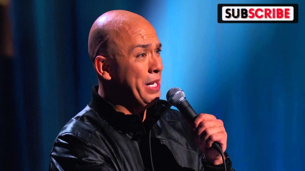 Jo Koy comic routine talking into mic pulling strange face with a bald head