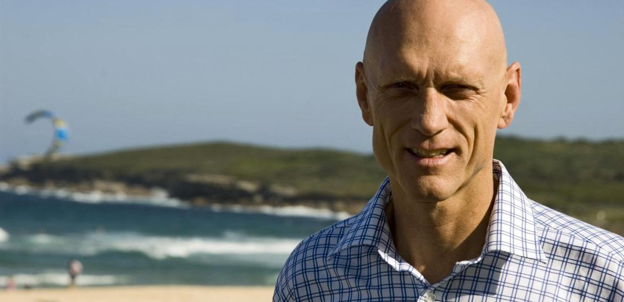 Peter Garrett at a beach with parasailer in background