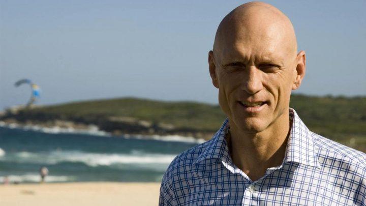 Peter Garrett bald Australian musician politician at the beach with parasailer in background