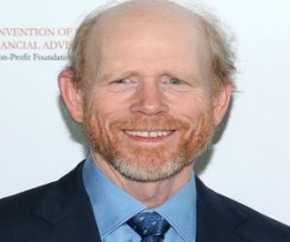 Ron Howard smiling wearing blue suit shirt and tie