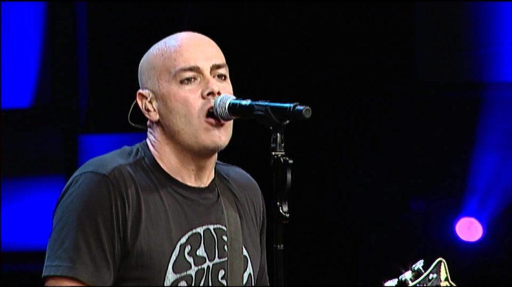 Peter Furler singing while playing guitar