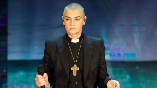 Sinead O'Connor wearing a Catholic priests uniform with shaved head hair