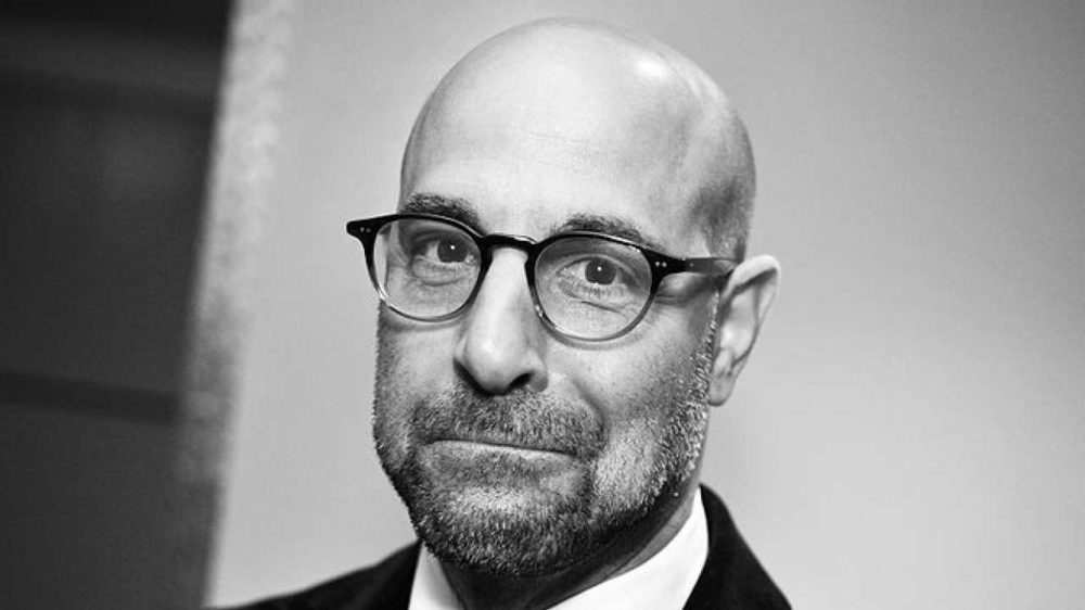 Stanley Tucci pictured bald head wearing glasses and sporting designer beard stubble