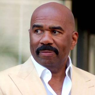 Steve Harvey bald black tv host with big moustache