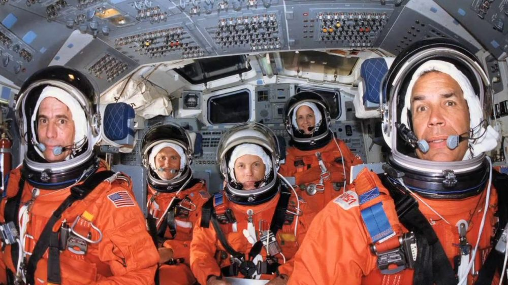 Story Musgrave with fellow American astronauts wearing spacesuits