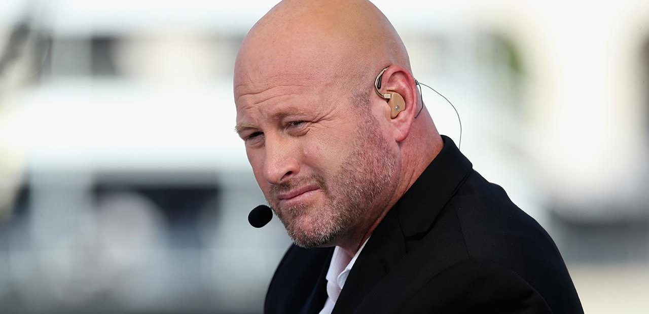 Trent Dilfer sporting scruff beard and wearing ear piece and microphone