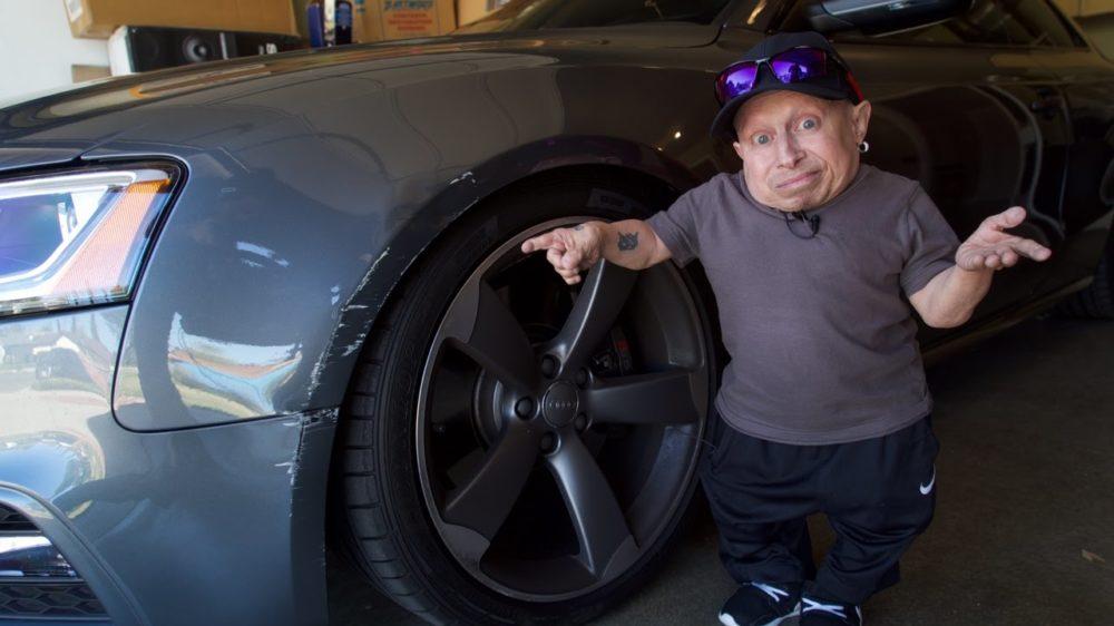 Verne Troyer pointing at damaged car