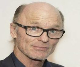 Ed Harris bald head wearing spectacles
